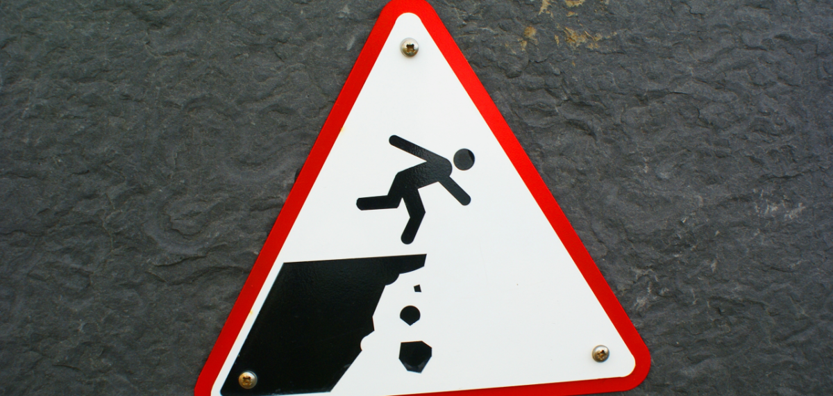 sign of a man ready to fall off a cliff